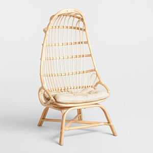 Natural rattan cocoon chair with white cushion inside. photo