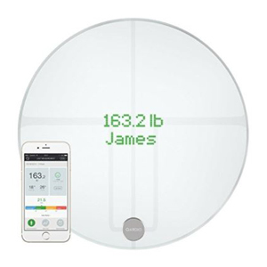 Clear round digital scale with smartphone showing wireless capabilities. photo