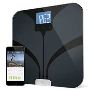 Black digital scale with smartphone showing bluetooth capabilities. photo