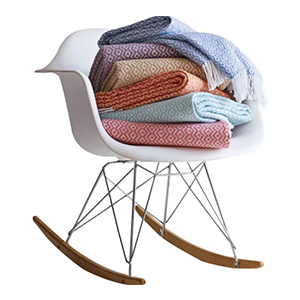 Geometric-patterned throw blankets in blue, purple, tan, orange, and red piled on a white chair photo
