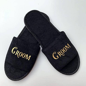 Black fuzzy open-toe slippers with groom written in gold on the tops photo