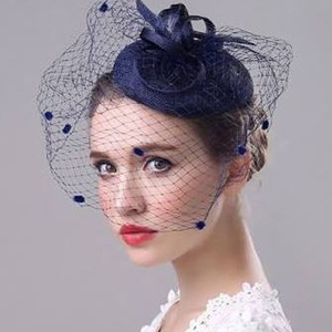 Navy blue birdcage headpiece with small hat on top. photo