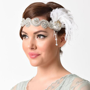 Woman wearing a beaded headband with white feathers on the side. photo
