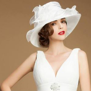 Woman wearing a wedding dress and a white wide-brim hat. photo