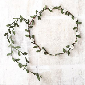 Twine head piece with greenery and small white flowers all around it. photo