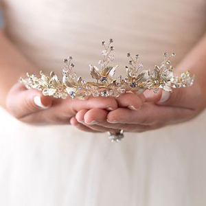 Woman holding the gold floral tiara while wearing a wedding dress. photo