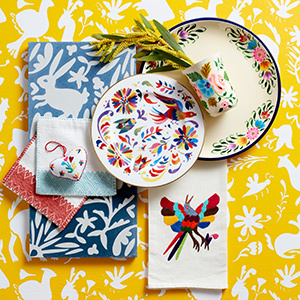 Yellow floral background with colorful plates and napkins on it. photo