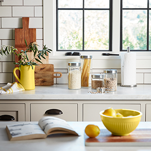 Kitchen with white subway tile backsplash and canisters full of grain. photo