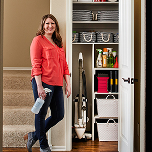Woman standing next to an organized cleaning closet. photo