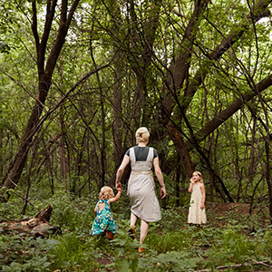 Woman walking in a wooded area with her two daughters. photo