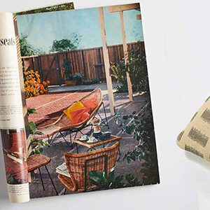 An old magazine laying on a gray background next to a throw pillow. photo