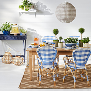 Wooden table with blue plaid chairs, leather lanterns, and navy blue planter on the side photo