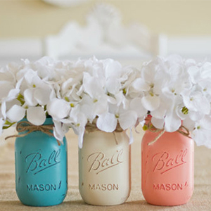 Turquoise, cream, and peach painted mason jars filled with white hydrangeas photo