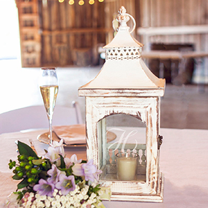 White distressed wooden lantern with monogrammed glass door and small candle inside photo
