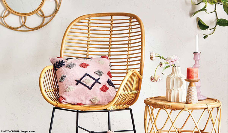 Southwestern-style seating with pink tribal throw pillow on a rattan chair next to a rattan side table with white and pink vases on it photo