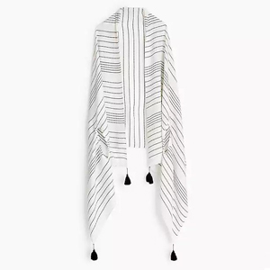 White cape scarf with black stripes and black tassel details. photo
