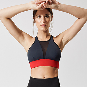 Blue sports bra with black mesh in the center and wide red band photo