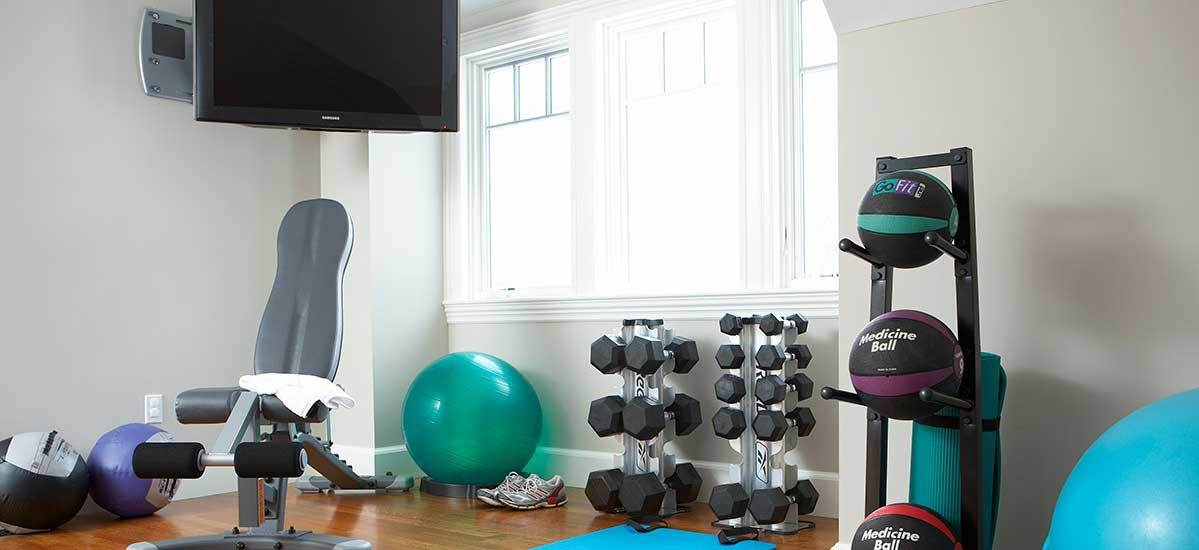 Home gym with dumbbell set, medicine balls, yoga balls, weight bench, and mounted TV