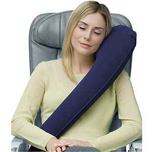 Woman sitting in a seat with a long travel pillow that goes across her body and cradles her head at the shoulder photo