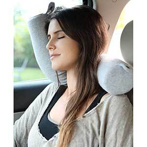 Woman sleeping in the car with a long, cylindrical travel pillow that can twist into different positions photo