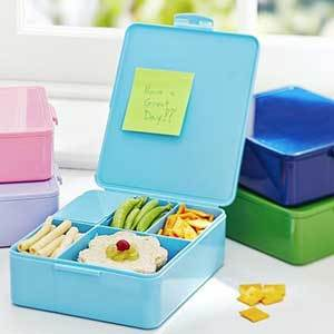 Blue bento box-style lunch container sitting on a white counter with other colorful bento boxes from Pottery Barn photo
