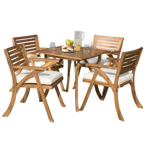 Outdoor dining set includes square wooden table and four wooden chairs with white cushions. photo