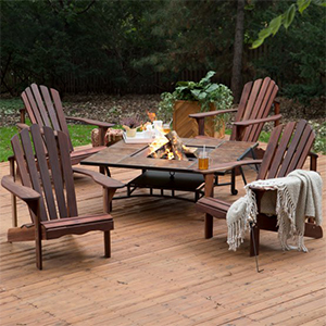 Four Adirondack wooden chairs around a natural wood fire pit table photo