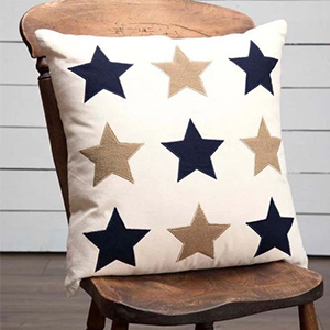 Cream square pillow with navy and gold star appliques on it photo