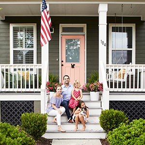 Family of four sitting on porch steps with dog photo