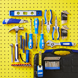 Blue tools on a yellow pegboard photo