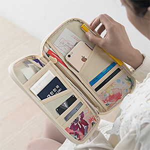 Woman holding a floral travel wallet opened to inside showing multiple slots and compartments filled with credit cards and a cell phone photo