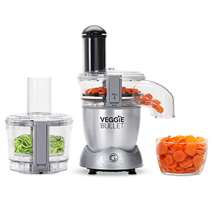 A silver veggie magic bullet in the middle of a glass bowl of chopped carrots and chopped celery photo
