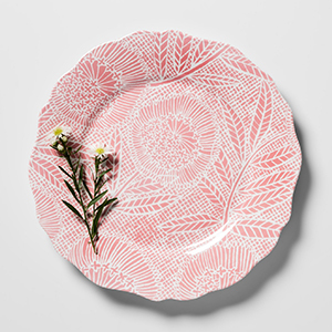 Light pink melamine plate with white floral design on it. photo