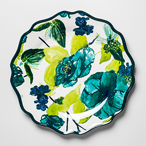 A white plate with a teal border and floral print that includes hues of blues and greens. photo