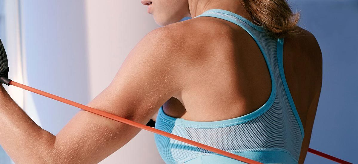 Close-up of woman in a light bra sports bra using a red resistance band for her arm workout.