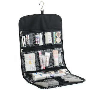 Black hanging makeup organizer with clear pockets filled with a variety of makeup products photo