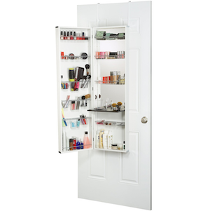 Mirror with built-in makeup organizer on Amazon filled with products hanging on the back of a white door photo
