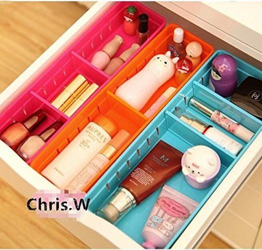 Removable tray makeup organizer in pink, orange, and blue in a white drawer photo