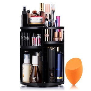 A black rotating makeup organizer filled with beauty products and a orange beauty blender next to it photo