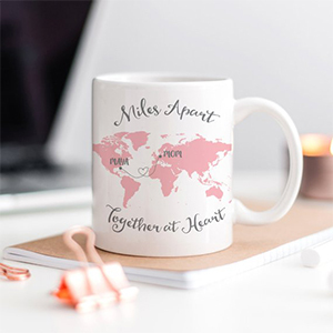 Best Coffee Mugs, pink and white Personalized World Map Mug sitting on top of a notebook photo
