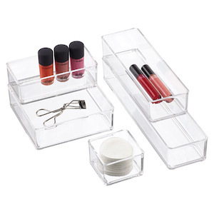 Acrylic stackable drawer organizers with lipgloss, cotton pads, and an eyelash curler inside photo