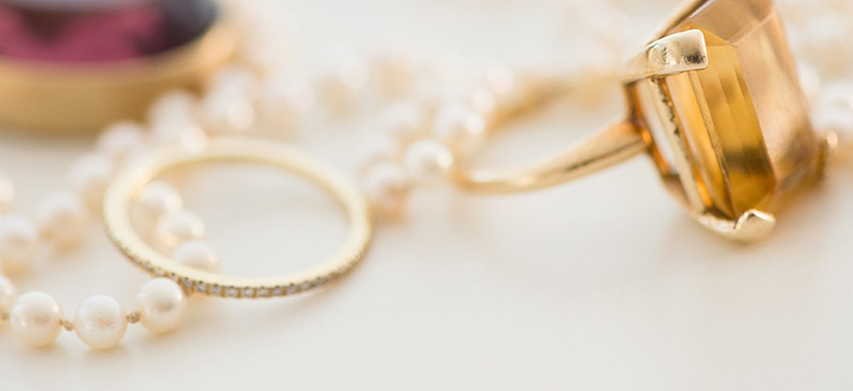 Two rings and a string of pearls sit close together