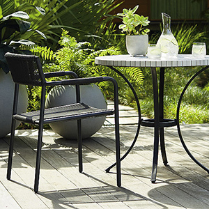 Patio Furniture, black Hexa Bistro Table and Chairs with plants in the background photo