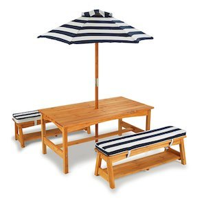 A long wooden table with a stiped umbrella and a striped cushion wooden bench on each side photo