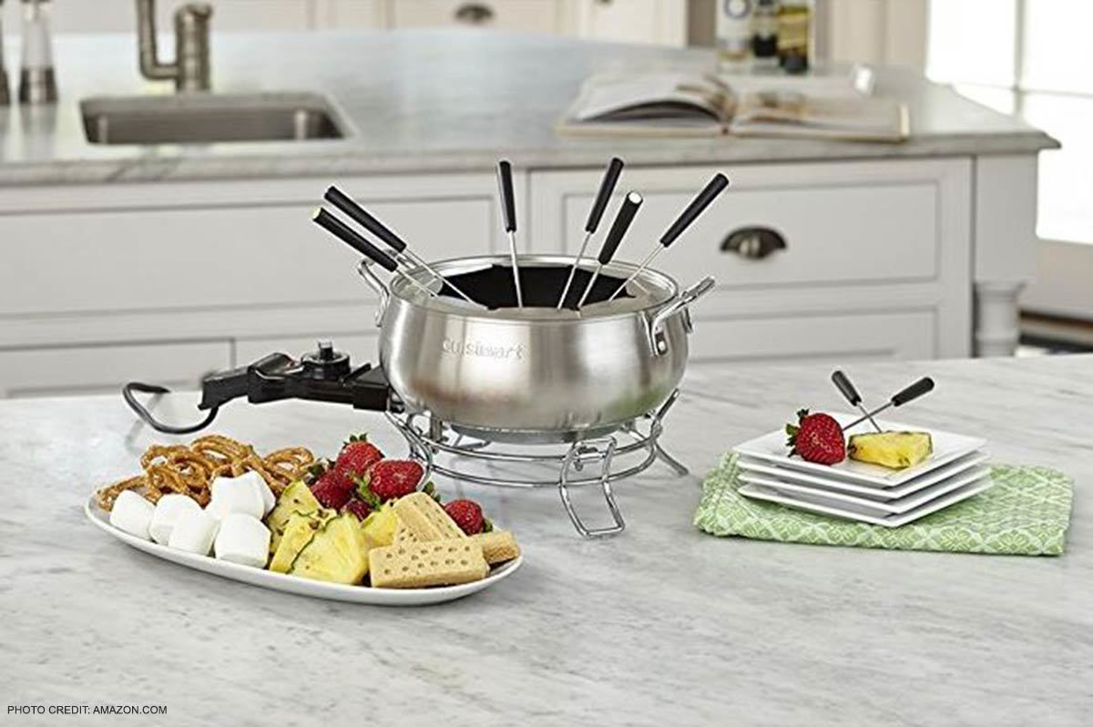 Cuisinart electric fondue pot on kitchen counter with a platter of marshmallows, pretzels, strawberries, pineapples, and bread for dipping and square plates to eat them on. photo