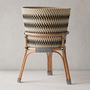 Striped rattan plant stand with bamboo legs. photo