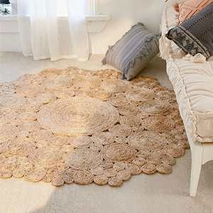 Camilla Round Jute Area Rug in in caramel brown color on the floor next to a bench photo