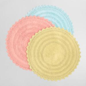 Three area rug bath mats stacked on top of each other in yellow, pink, and blue photo