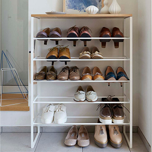 White shoe organizer with six tiers filled with a variety of shoes. photo