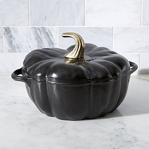 Black cast iron cocotte shaped like a pumpkin with a gold stem from Crate and Barrel photo